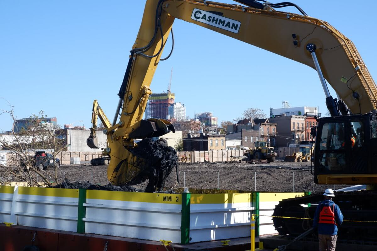 """A crane scoops """"black mayonnaise"""" out of the Gowanus Canal. Two treatment facilities, Owls Head and Head end, endeavor to keep the sludge out of the canal entirely."""